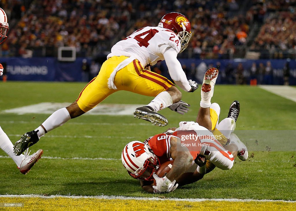 John Plattenburg #24 of the USC Trojans leaps over Corey Clement #6 of the Wisconsin Badgers as he scores a touchdown during the second quarter of the National University Holiday Bowl at Qualcomm Stadium on December 30, 2015 in San Diego, California.