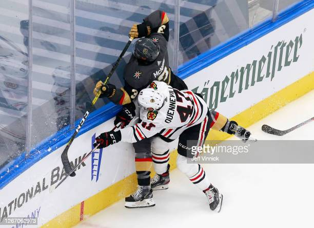 John Quenneville of the Chicago Blackhawks checks Brayden McNabb of the Vegas Golden Knights into the boards during the first period in Game Five of...