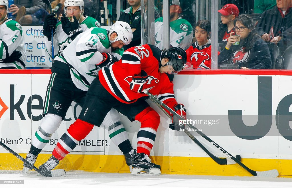 John Quenneville #42 of the New Jersey Devils and Jamie Benn #14 of the Dallas Stars battle for control of the puck during the game on March 26, 2017 at Prudential Center in Newark, New Jersey.