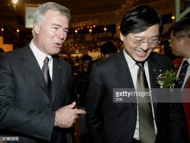 John R Joyce Senior Vice President and Group Executive of IBM Global Services shares a joke with Chinese computer maker Lenovo Group President and...