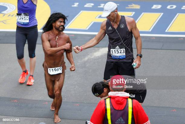 John Raines left and Thomas J Motherway fist bump after crossing the finish line of the 121st Boston Marathon in Boston on Apr 17 2017