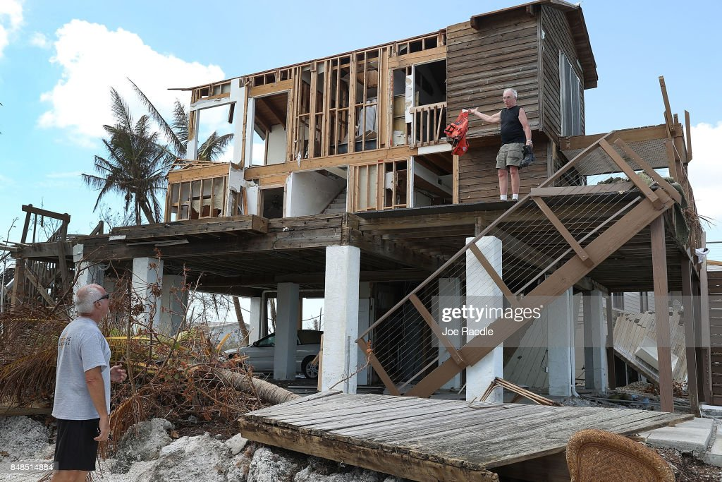 John Rhode talks with his neighbor Paul Sosbey (L) as he attempts to salvage what he can from his home that was destroyed by hurricane Irma on September 17, 2017 in Summerland Key, Florida. The Federal Emergency Management Agency has reported that 25-percent of all homes in the Florida Keys were destroyed and 65-percent sustained major damage when they took a direct hit from Hurricane Irma.