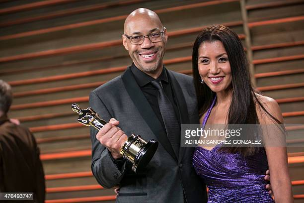 John Ridley flanked by his wife Gayle holds his Academy Award for best adapted screenplay for 12 Years a Slave as he arrives to the 2014 Vanity Fair...