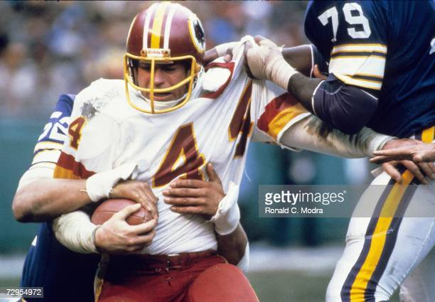 John Riggins of the Washington Redskins carries the ball as Doug Martin of the Minnesota Vikings grabs his jersey during the NFC Divisional Playoff...