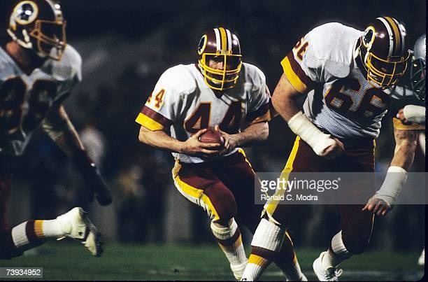 John Riggins of the Washington Redskins carries the ball during Super Bowl XVIII against the Oakland Raiders on January 22 1984 in Tampa Florida