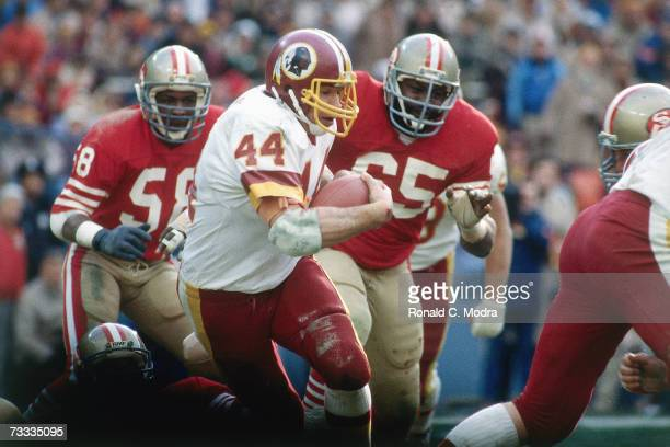 John Riggins of the Washington Redskins carries the ball with Laurence Pillars and Keena Turner of the San Francisco 49ers trying to catch him during...