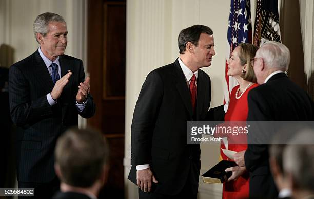 John Roberts, center, kisses his wife Jane after he was sworn in as the 17th chief justice of the United States by Supreme Court Associate Justice...