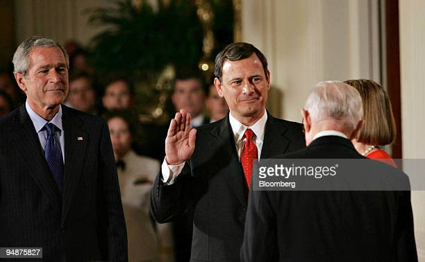 John Roberts holds up his right hand as he is sworn in as the 17th Chief Justice of the U.S. Supreme Court by Supreme Court Justice John Paul...