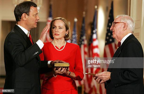 John Roberts is sworn in as Chief Justice of the US by Associate Justice John Paul Stevens as Roberts' wife Jane Roberts holds a bible during a...