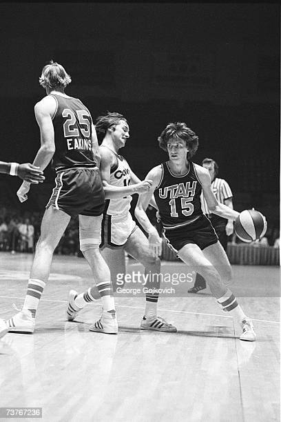 John Roche of the Utah Stars drives past Louie Dampier of the Kentucky Colonels with help from Jim Eakins during an American Basketball Association...