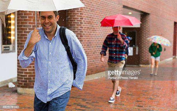 John Rogers, of Alexandria, Virginia, leads a line of umbrella-carrying pedestrians on Middle Street on Tuesday during torrential rain. Rogers is...