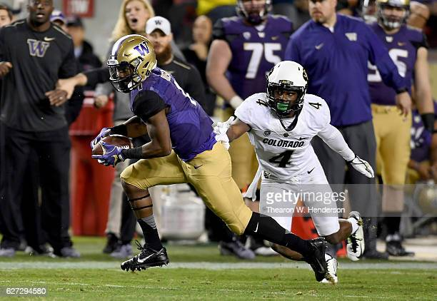 John Ross of the Washington Huskies gets past Chidobe Awuzie of the Colorado Buffaloes on his way to scoring a touchdown during the Pac12...