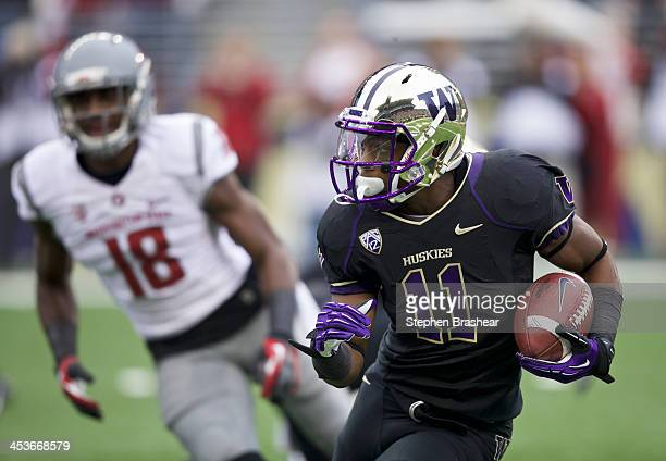 John Ross of Washington returns a kickoff during the first half of a game against Washington State Cougars at Husky Stadium on November 29 2013 in...