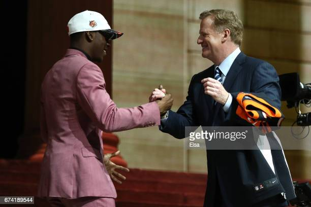 John Ross of Washington shakes hands with Commissioner of the National Football League Roger Goodell after being picked overall by the Cincinnati...