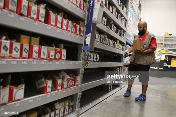 John Ruiz restocks a shelf at a Lowe's store on the day the company reported a rise in earnings on March 1 2017 in Hialeah Florida Lowe's reported...