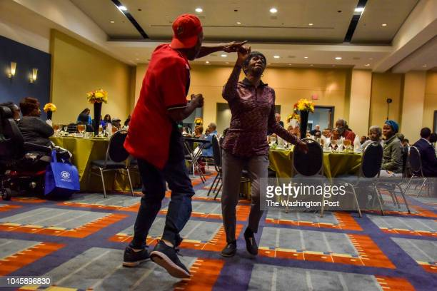 John Russell, L, and Bertha Winters share a dance as seniors displaced by the devastating fire at the Arthur Capper Senior Apartments attend a...