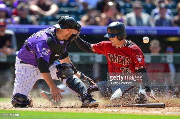 John Ryan Murphy of the Arizona Diamondbacks slides safely into home as Chris Iannetta of the Colorado Rockies attempts to apply a tag in the sixth...