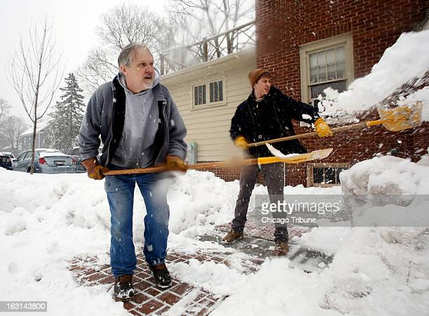 John Rygiewicz left North Central College heads groundskeeper and parttime helper Tommy Lusk shovel the walkways around school buildings Tuesday...