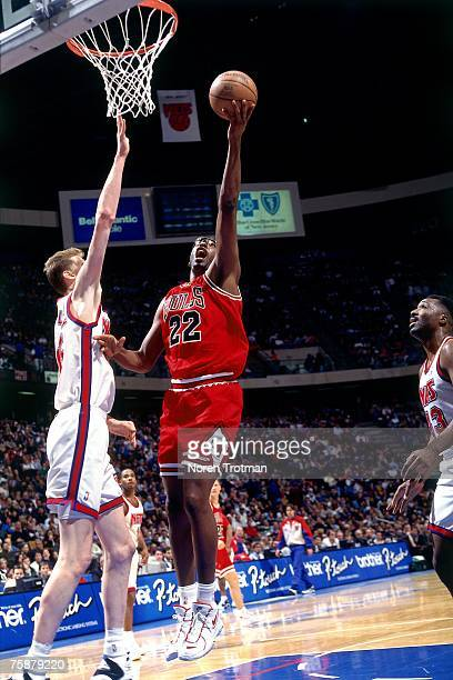 John Salley of the Chicago Bulls attempts a layup against Shawn Bradley of the New Jersey Nets during a 1996 NBA Game at Brendan Byrne Arena in East...
