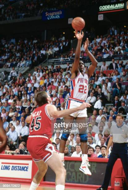 John Salley of the Detroit Pistons shoots over Ed Nealy of the Chicago Bulls during an NBA basketball game circa 1990 at the The Palace of Auburn...