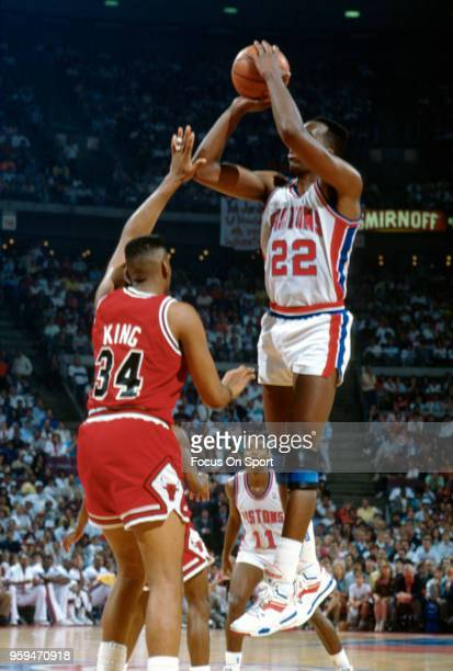 John Salley of the Detroit Pistons shoots over Stacey King of the Chicago Bulls during an NBA basketball game circa 1990 at the The Palace of Auburn...