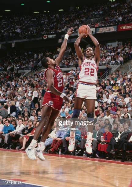 John Salley, Power Forward for the Detroit Pistons attempts a three point shot as Ron Anderson, Small Forward for the Philadelphia 76ers reaches to...