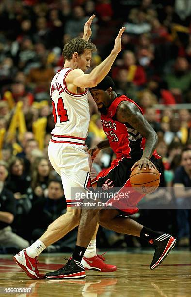 John Salmons of the Toronto Raptors runs into Mike Dunleavy of the Chicago Bulls at the United Center on December 14 2013 in Chicago Illinois The...