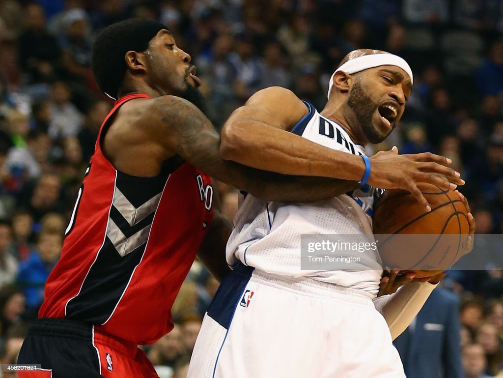 John Salmons #25 of the Toronto Raptors scrambles for the ball against Vince Carter #25 of the Dallas Mavericks at American Airlines Center on December 20, 2013 in Dallas, Texas.