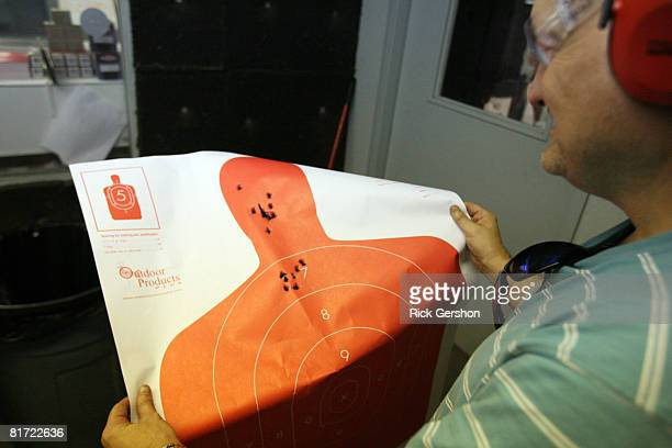 John Sanders of Irving TX checks his target after shooting his glock pistol June 26th at the DFW Gun Range and Training Center in Dallas Texas The US...