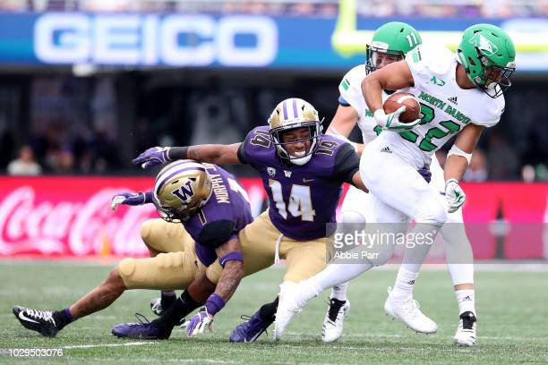 John Santiago of the North Dakota Fighting Sioux breaks a tackle against JoJo McIntosh of the Washington Huskies in the second quarter during their...