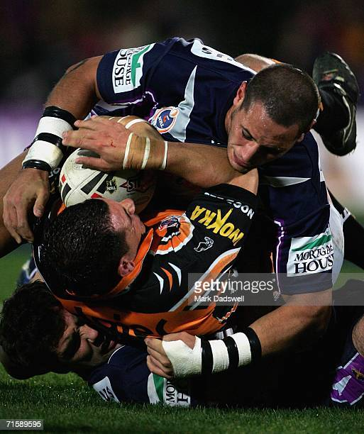 John Scandalis of the Tigers is wrapped up in a tackle during the round 22 NRL match between the Melbourne Storm and the Wests Tigers at Olympic Park...