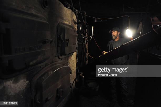 John Schertz of John's Outback Coal Boiler Service checks the broken coal boiler at the basement of school gym Silverton's K12 school has been...