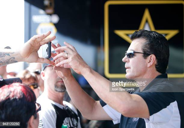 John Schnatter Founder and Chairman of the Board for Papa John's Pizza reaches for a fan's cell phone before a charity exhibition race against Antron...