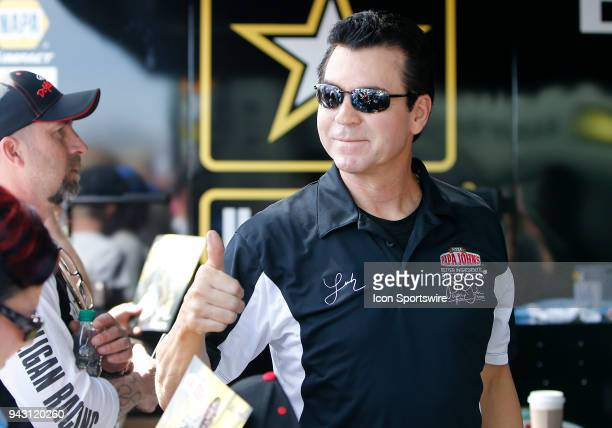 John Schnatter Founder and Chairman of the Board for Papa John's Pizza gives a thumbs up before a charity exhibition race against Antron Brown during...