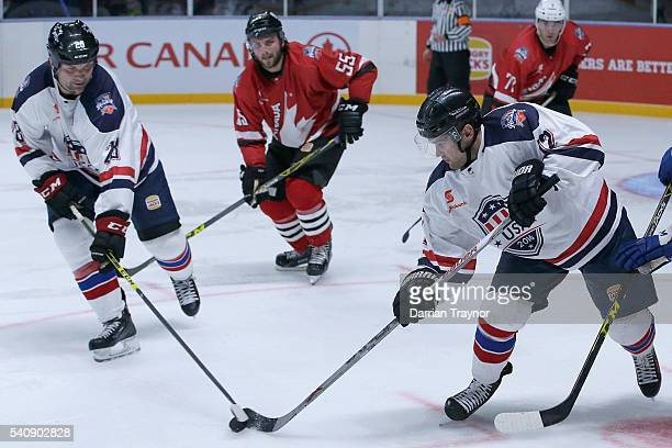 John Scott and Joe Harcharik of USA protect the puck during the match between Team USA and Team Canada at Rod Laver Arena on June 17 2016 in...