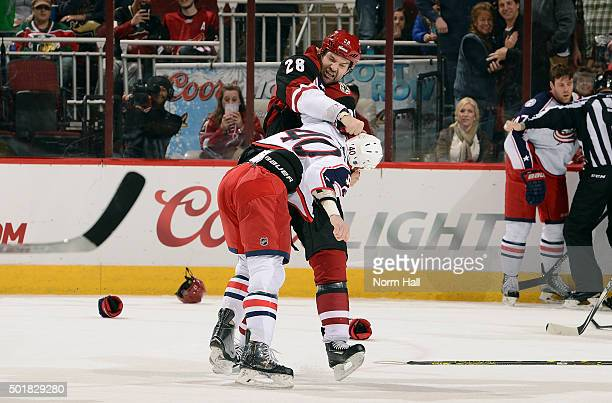 John Scott of the Arizona Coyotes and Jared Boll of the Columbus Blue Jackets tangle during the second period at Gila River Arena on December 17 2015...
