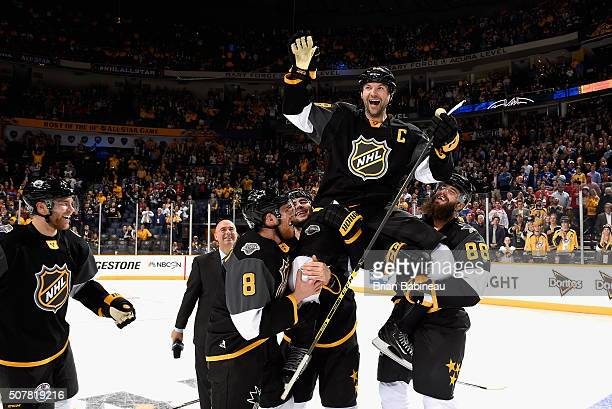 John Scott of the Arizona Coyotes is held up by teammates Mark Giordano of the Calgary Flames and Brent Burns and Joe Pavelski of the San Jose Sharks...