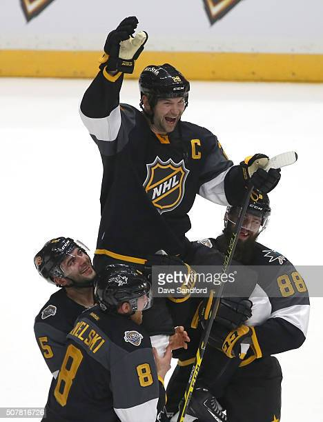 John Scott of the Arizona Coyotes is held up byteammates Mark Giordano of the Calgary Flames and Brent Burns and Joe Pavelski of the San Jose Sharks...