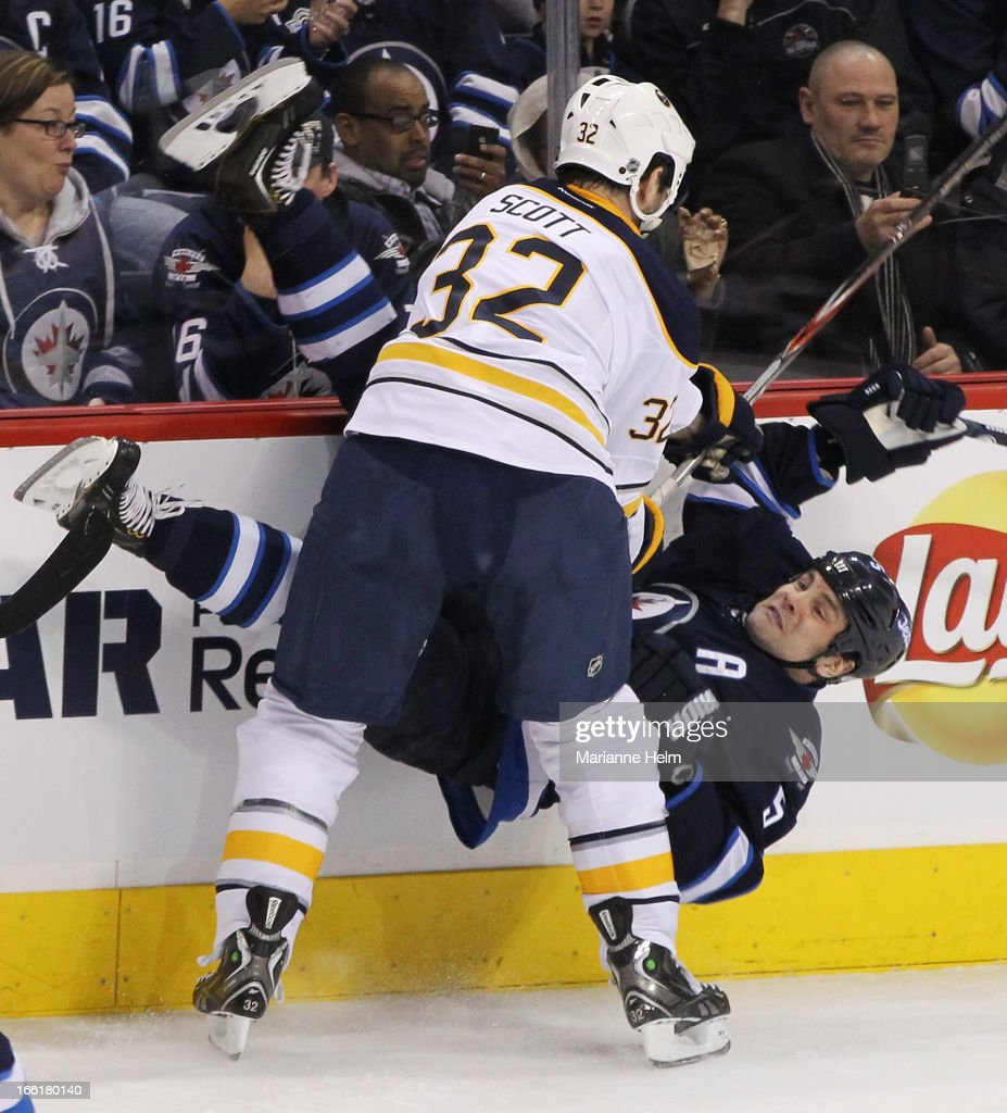 John Scott #32 of the Buffalo Sabres takes down Mark Stuart #5 of the Winnipeg Jets during first-period action in a game against the Buffalo Sabres on April 9, 2013 at the MTS Centre in Winnipeg, Manitoba, Canada.