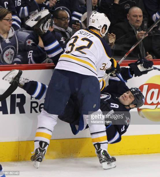 John Scott of the Buffalo Sabres takes down Mark Stuart of the Winnipeg Jets during first-period action in a game against the Buffalo Sabres on April...