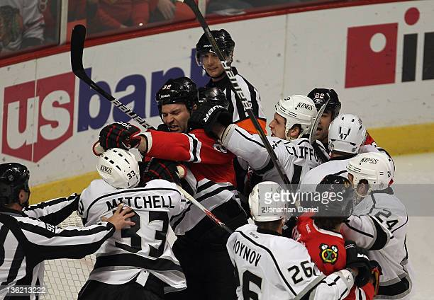 John Scott of the Chicago Blackhawks scuffles with Willie Mitchell and Kyle Clifford of the Los Angeles Kings at the United Center on December 28...