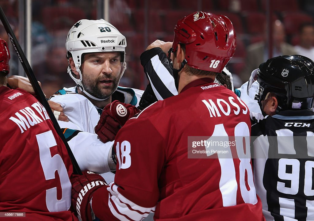 John Scott #20 of the San Jose Sharks scrums with David Moss #18 of the Arizona Coyotes during the preseason NHL game at Gila River Arena on October 3, 2014 in Glendale, Arizona. The Sharks defeated the Coyotes 3-1.