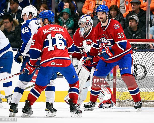 John Scott of the St John's IceCaps helps Mark MacMillan of the St John's IceCaps protect the crease against the Toronto Marlies during game action...