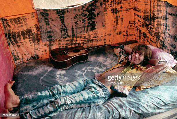 John Sebastian cofounder of the band the Lovin' Spoonful lies on a bed covered with tiedyed sheets