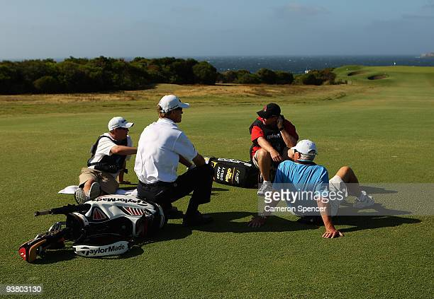 John Senden of Australia and caddies sit on the 13th fairway as play is suspended due to prevailing winds during the second round of the 2009...