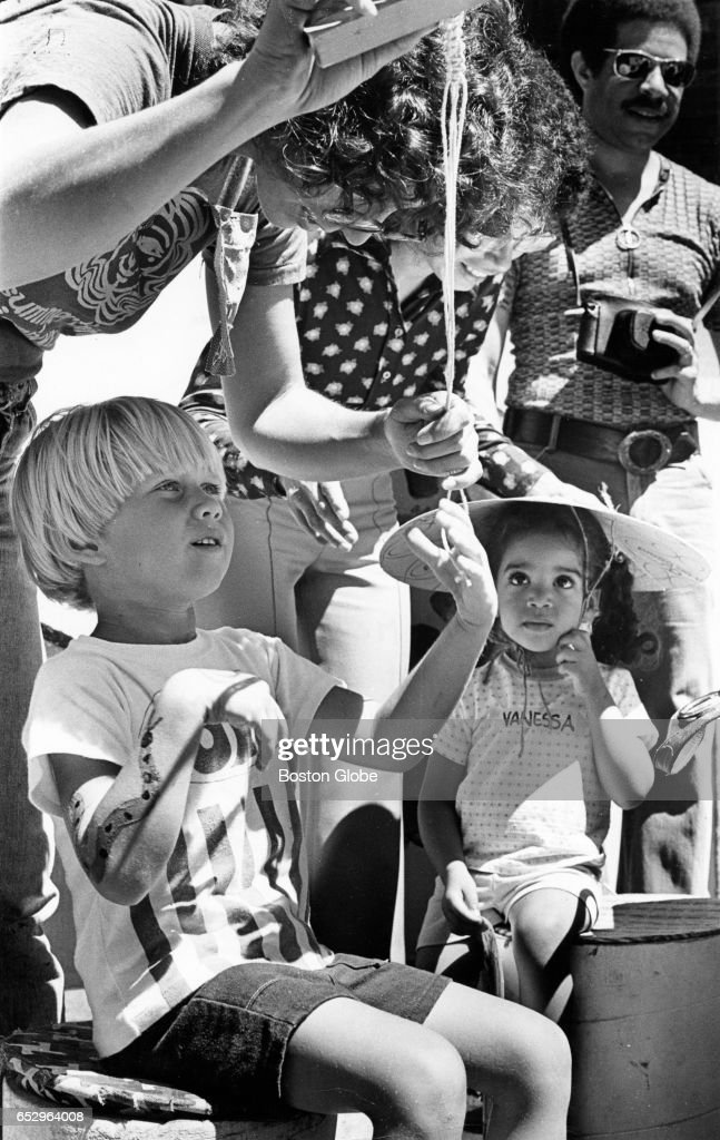 John Shehan, 5 1/2, learns macrame from Joy Silverstine while Vanessa Wesley, 2, watches, wearing a homemade hat, during a Summerthing event in Boston on Aug. 11, 1974.