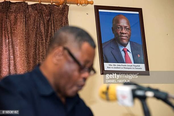 John Shibuda who heads the Uwaka group of small opposition parties speaks under a portrait of new Tanzanian president John Magufuli at a press...