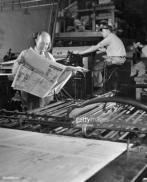John Sidey the editor of the Adair County Free Press checks the proofs of a newspaper in the printing press room