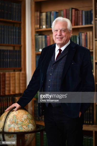 John Simpson posing with a globe for a portrait in the Cambridge Union on May 2 2018 in Cambridge England