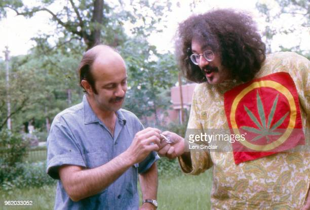 John Sinclair political activist wearing a large cannabis plant patch smoking marijuana outdoors with John Rosevear in Ann Arbor MI in 1968